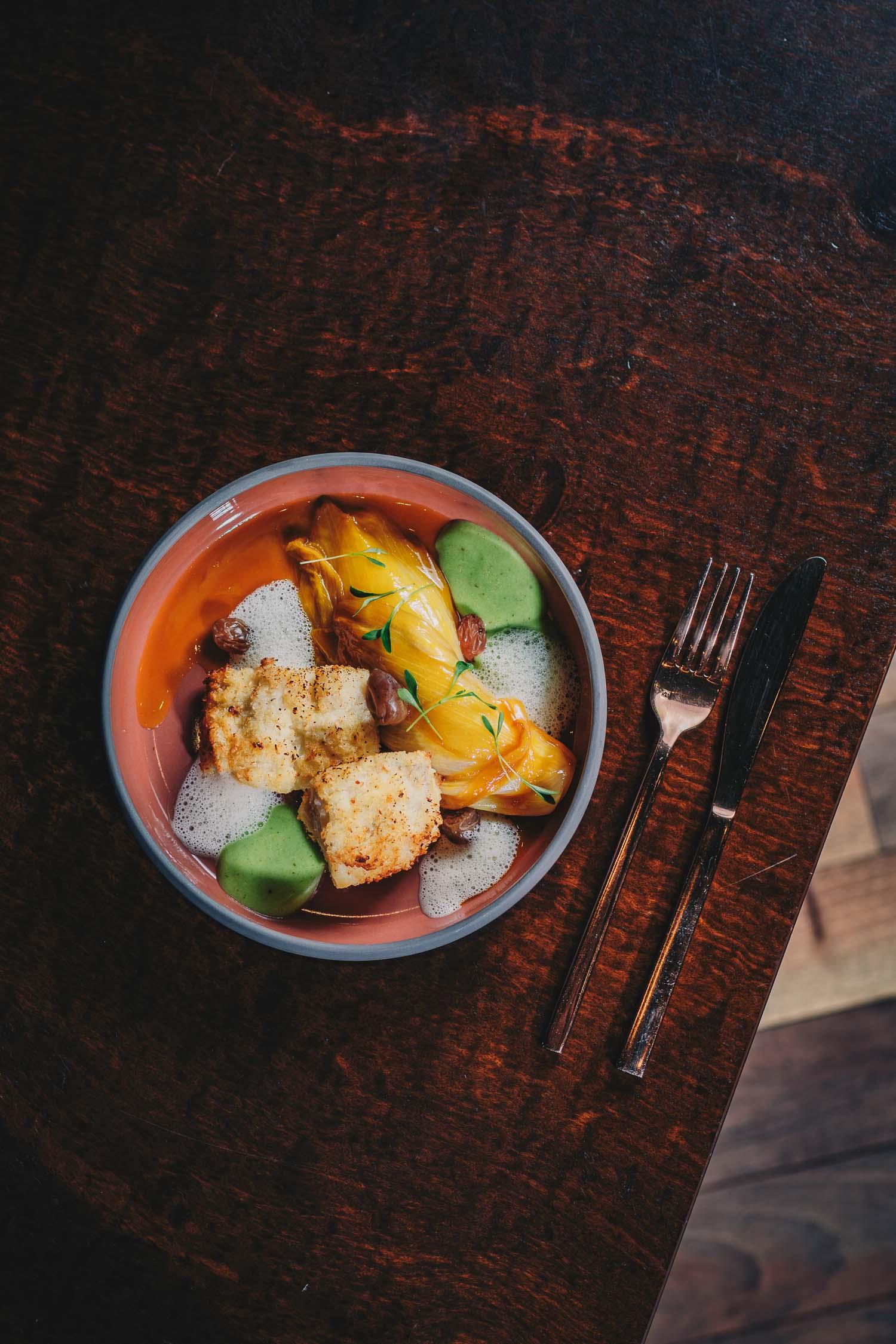 Fischstäbchen mit Kokosmatten, Orangenchicorée, getrocknete Trauben, Kräutersauce und Fischschaum